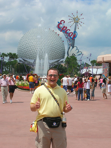 man wearing fanny pack and tourist clothes smiles in front of disney epcot center and crowd