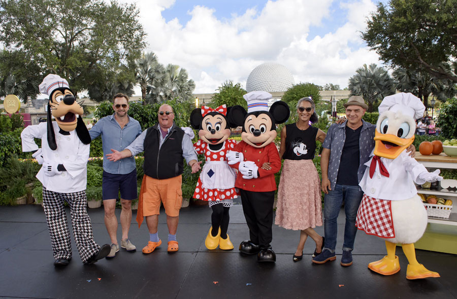 """The Chew"" co-hosts (l-r) Clinton Kelly, Mario Batali, Carla Hall and Michael Symon pose with Goofy, Minnie Mouse, Mickey Mouse and Donald Duck during a week of filming at Walt Disney World Resort highlighting the Epcot International Food & Wine Festival."
