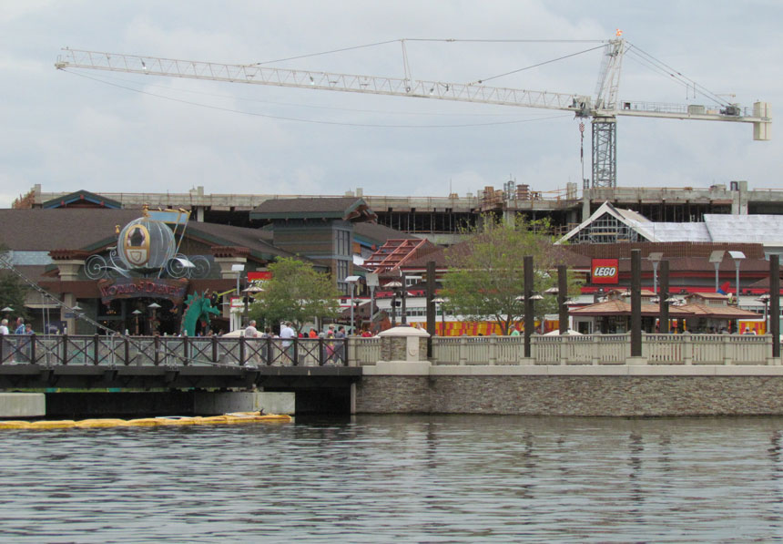 Construction looms behind The Lego Store and World of Disney at Disney Springs