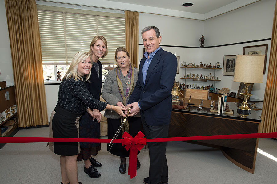 (From left) Walt Disney's granddaughters Michelle Lund, Jennifer Goff, and Joanna Miller with Disney Chairman and CEO Bob Iger cutting the ribbon at the dedication for restoration of Walt's office Suite on December, 7, 2015.