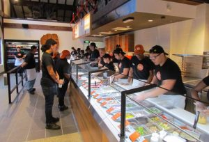 helpful staff preparing pizzas