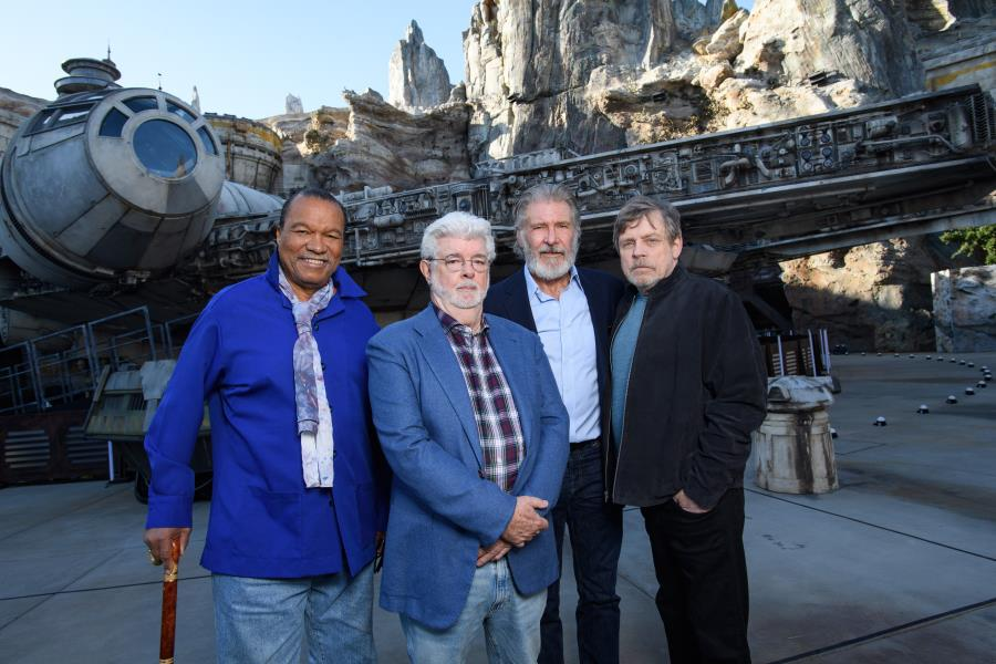 Billy Dee Williams, George Lucas, Harrison Ford and Mark Hamill pose in front of the Millennium Falcon at Star Wars: Galaxy's Edge