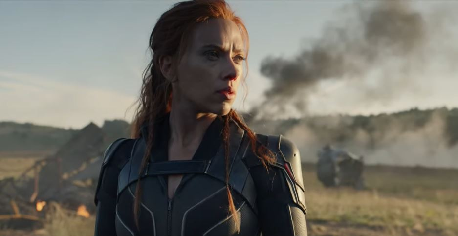 Natasha Romanoff gazes off into the distance in front of some smoking wreckage in Black Widow