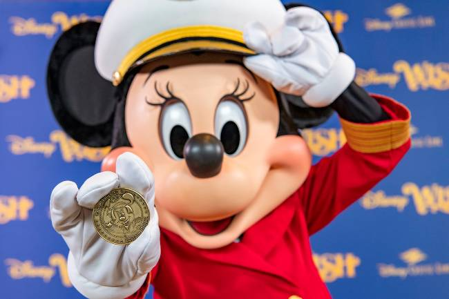 Captain Minnie holds the coin.